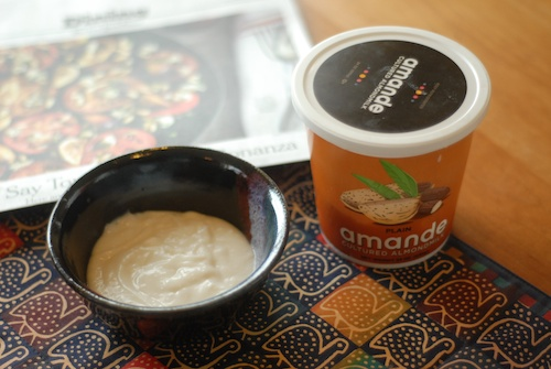 Amande almond milk yogurt shown in a bowl with container, place mat, and newspaper nearby