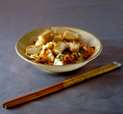 Asian style slaw shown in a bowl topped with tofu and with chopsticks nearby