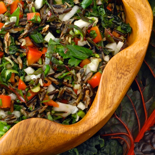 finished wild rice, kale and fennel salad shown in a wooden salad bowl with a chard leaf in the background