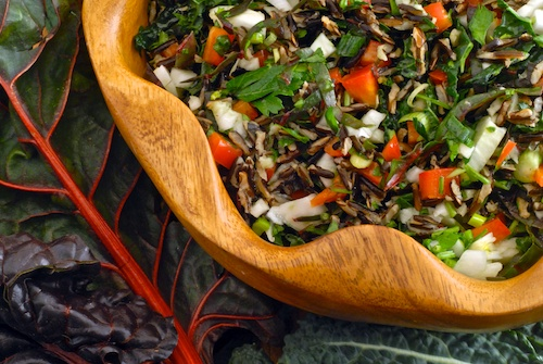 finished chard, kale, and fennel salad with wild rice shown in a wooden salad bowl with chard and kale leaves in the backgrounc