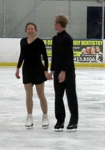 man in black outfit and woman in black skating dress skating