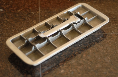 a stainless steel ice cube tray filled with coconut water ice cubes