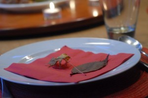 Thanksgiving dinner setting with red napkin and fall leaves