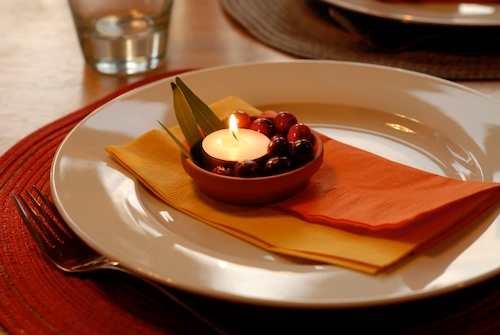 Thanksgiving table decorations: candle, cranberries, leaves, napkins on dinner plate