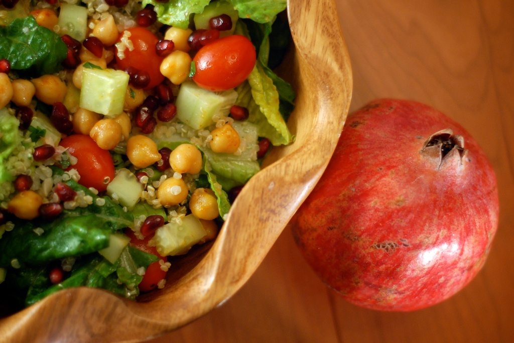 finished dinner salad containing quinoa tabbouleh, grape tomatoes, romaine lettuce, chickpeas and pomegranate shown in a wooden bowl with a pomegranate in the background