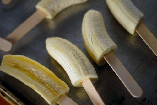 cut up bananas on popsicle sticks on a baking sheet