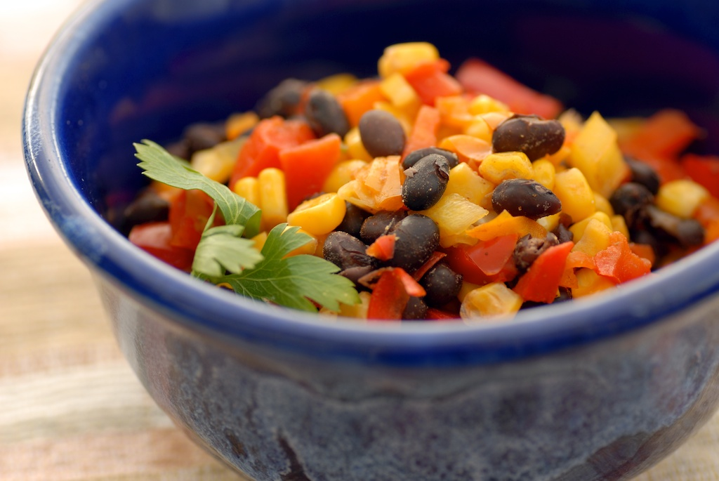 black bean, corn, and red bell pepper in a blue bowl with cilantro garnish