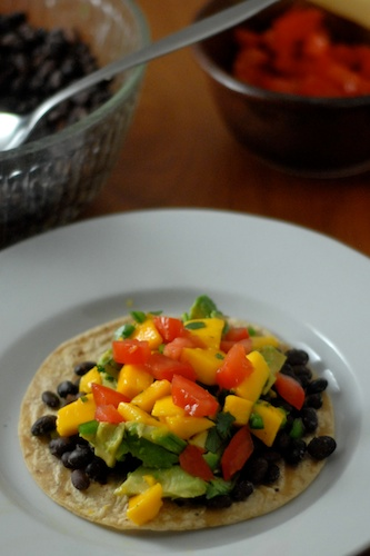 black bean tostada with mango salsa on a plate with black beans and tomatoes in the background