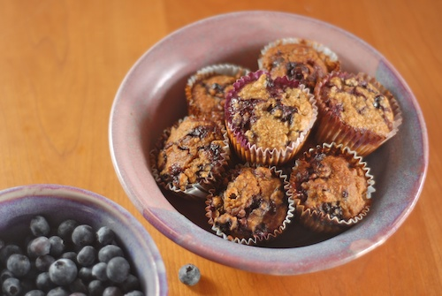 blueberry oatmeal muffins in a purple bowl with a bowl of blueberries nearby