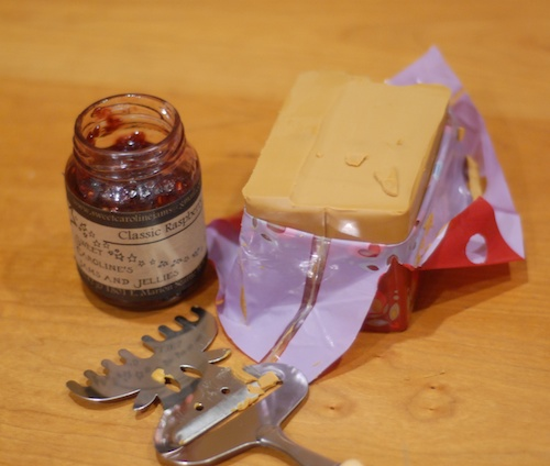 opened block of brunost cheese with jar of raspberry jam and cheese slicer