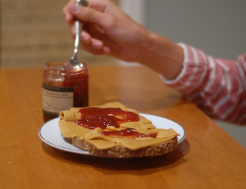 serving raspberry jam onto brunost on bread