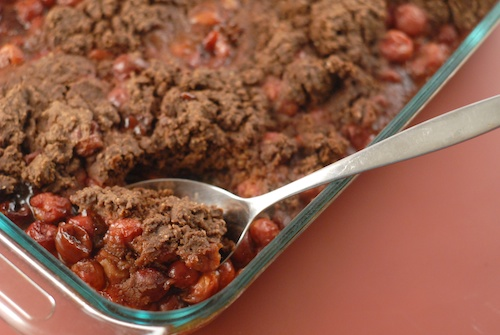 cherry chocolate cobbler shown in a baking dish with serving spoon