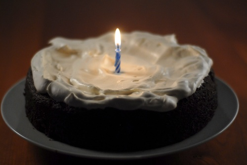 chocolate beer cake with one lit birthday candle