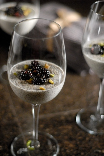 coconut chia pudding in a glass, topped with blackberries and slivered pistachios