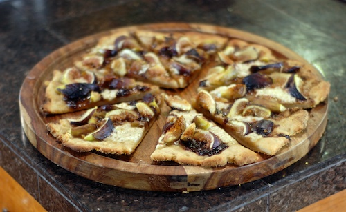 fig mascarpone dessert pizza shown sliced on a wooden plate