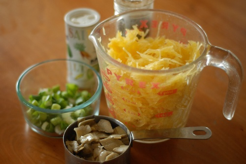 spaghetti squash strands in a measuring cup and other ingredients