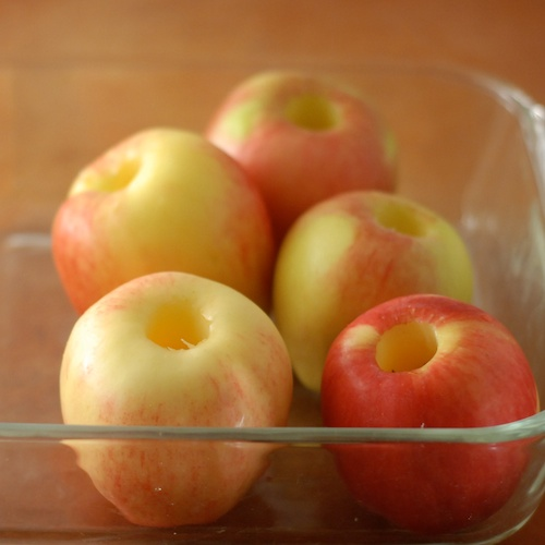 cored Pink Lady apples shown in glass baking dish