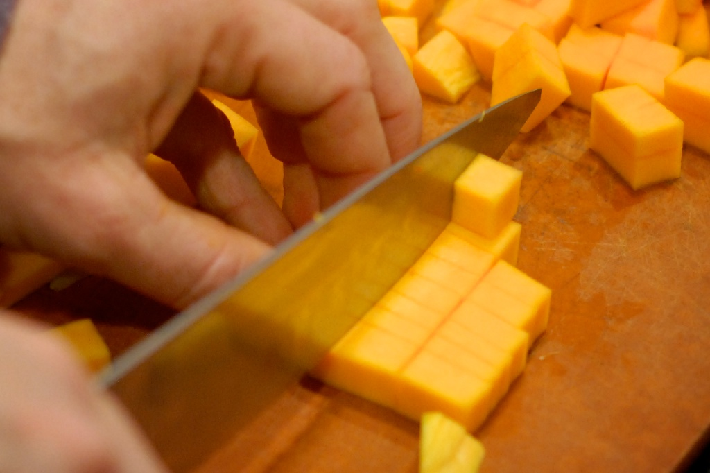 cutting sliced butternut squash into cubes
