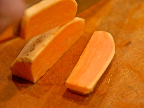 Sweet potato shown on a cutting board being cut into thin slabs with a chef's knife.