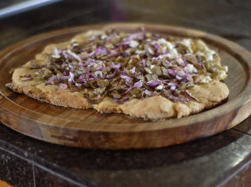 gluten free pizza topped with olives, red onions, artichoke hearts, and feta cheese on wooden serving plate