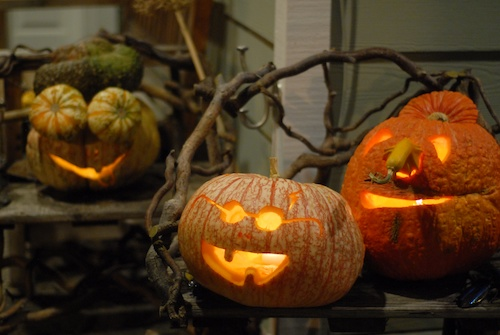 three carved pumpkins on a porch