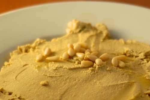 hummus with a topping of olive oil and pine nuts