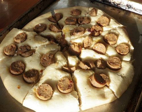 Greek lagana with vegetarian sausage on baking pan