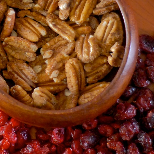 finished maple candied pecans in a wooden bowl with dried cranberries on the table in the background