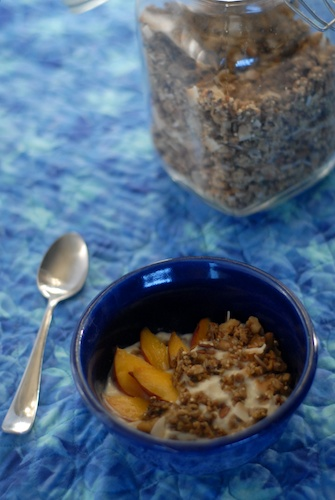 bowl of granola on yogurt with peaches, jar of granola in background