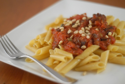 pasta puttanesca with raisins, olives, and pine nuts on a square dinner plate