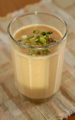 peach lassi in a glass, garnished with pistachios