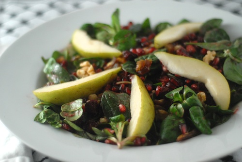 finished plate of salad with pear slices, pomegranate seeds, mache and baby spinach