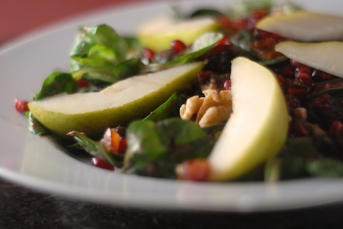 salad with pear slices, walnuts, pomegranates, dried cranberries and greens on a plate