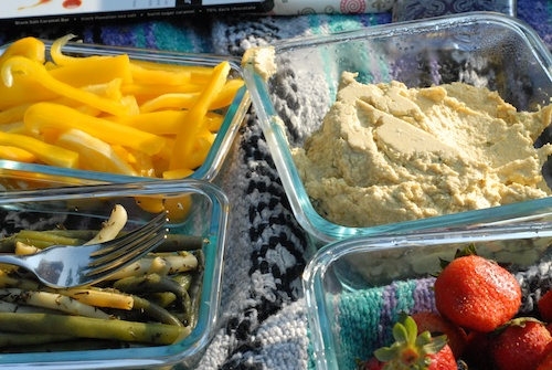 hummus, bell pepper strips, green beans, and strawberries in glass dishes on a picnic blanket