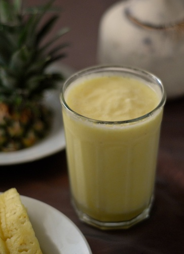 smoothie shown with pineapple top and young coconut in the background