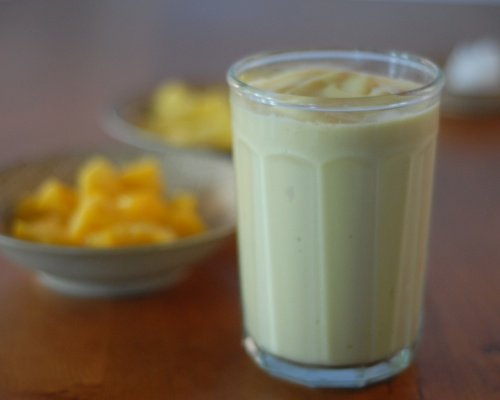 pineapple mango smoothie shown on a table with bowls of frozen fruit