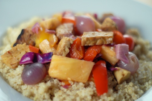pineapple tempeh bell pepper and pearl onion stir-fry on quinoa on dinner plate