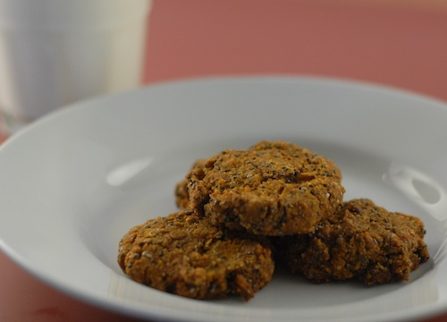 pumpkin chis chocolate chip cookies shown on a plate beside a glass of milk