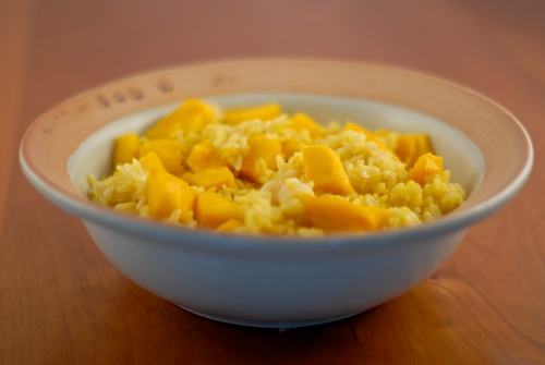 saffron rice with mangoes and macadamia nuts shown in a clay bowl