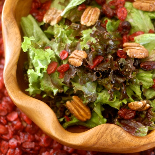 finished cranberry candied pecan salad in a wooden bowl with a background of dried cranberries