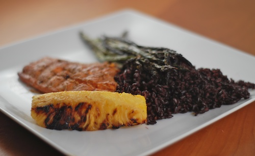 salmon on a plate with grilled pineapple, grilled asparagus and black rice