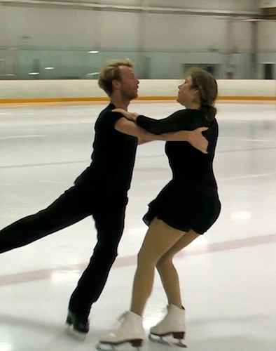 two skaters dressed in black ice dancing together