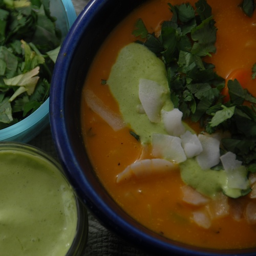 Sweet potato vegetable soup shown garnished with toasted coconut flakes chopped cilantro and cilantro lime garnish