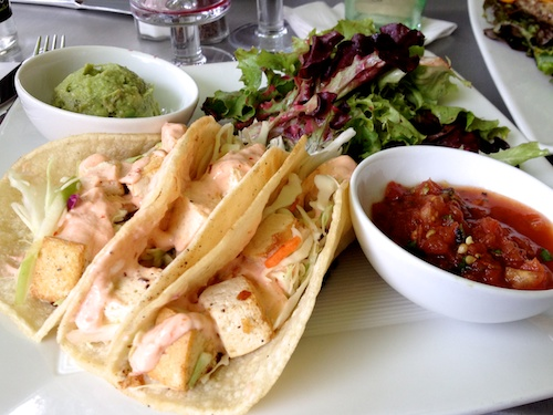 lunch plate with tofu tacos, bowls of roasted salsa and guacamole, green salad