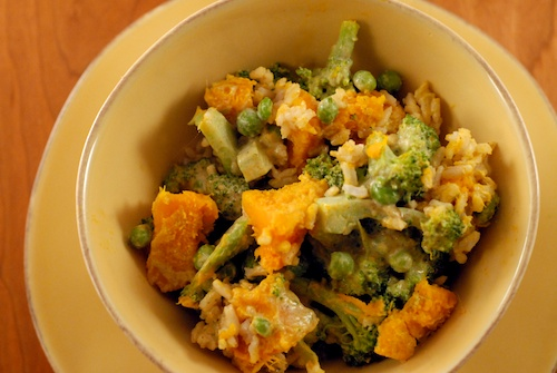veggie salad bowl with cubed red squash, steamed brocoli florets and stems, peas, and almond cilantro sesame dressing