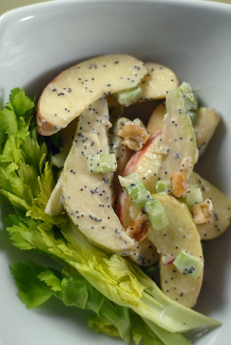 Waldorf salad with poppyseed dressing, celery greens, in white dish